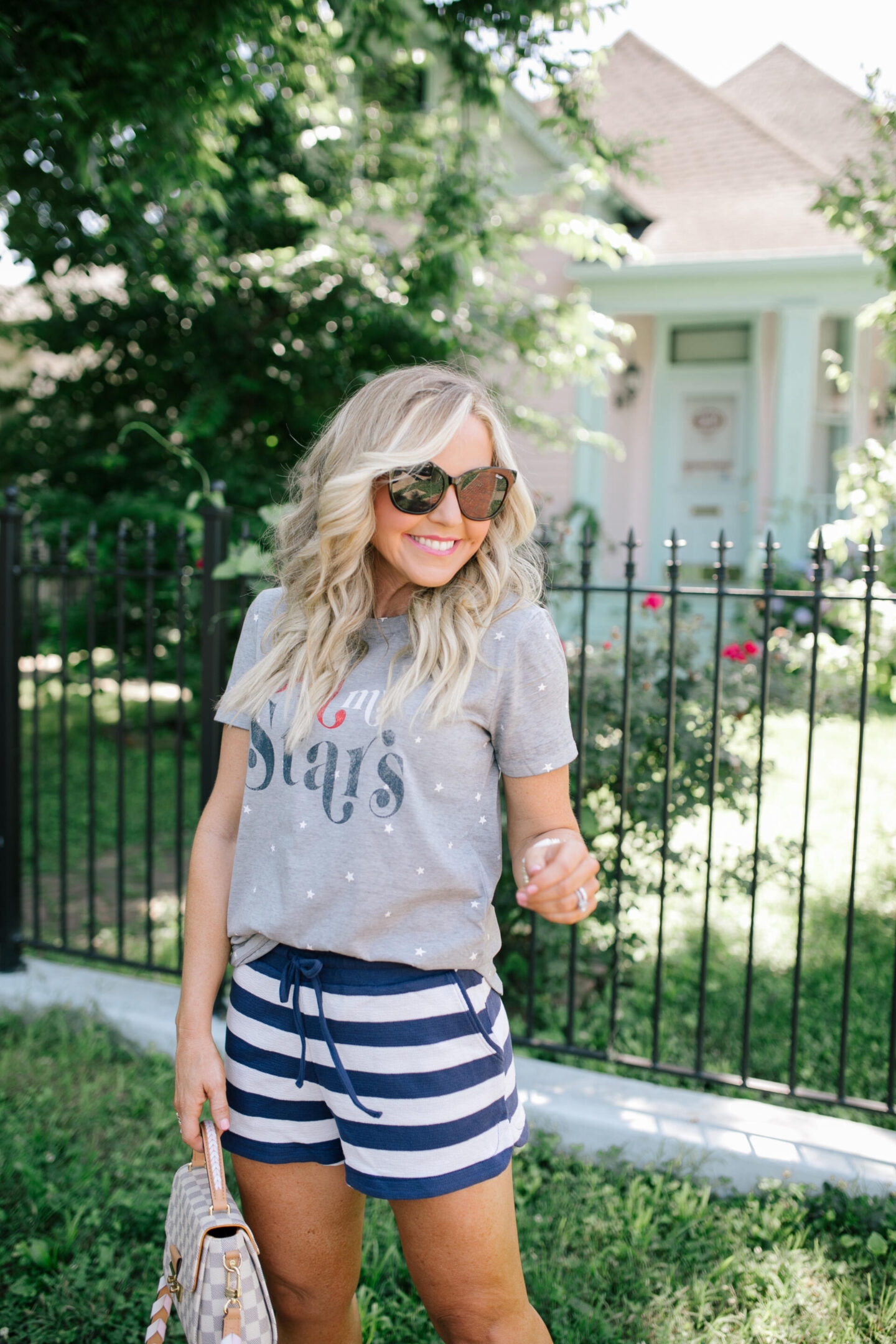 4th of July Outfits by popular Nashville fashion blog, Hello Happiness: image of a woman standing outside on a red brick walkway and wearing a grey Oh My Stars t-shrit with blue and white stripe shorts, sliver and white sneakers and holding a grey and white checkered handbag.