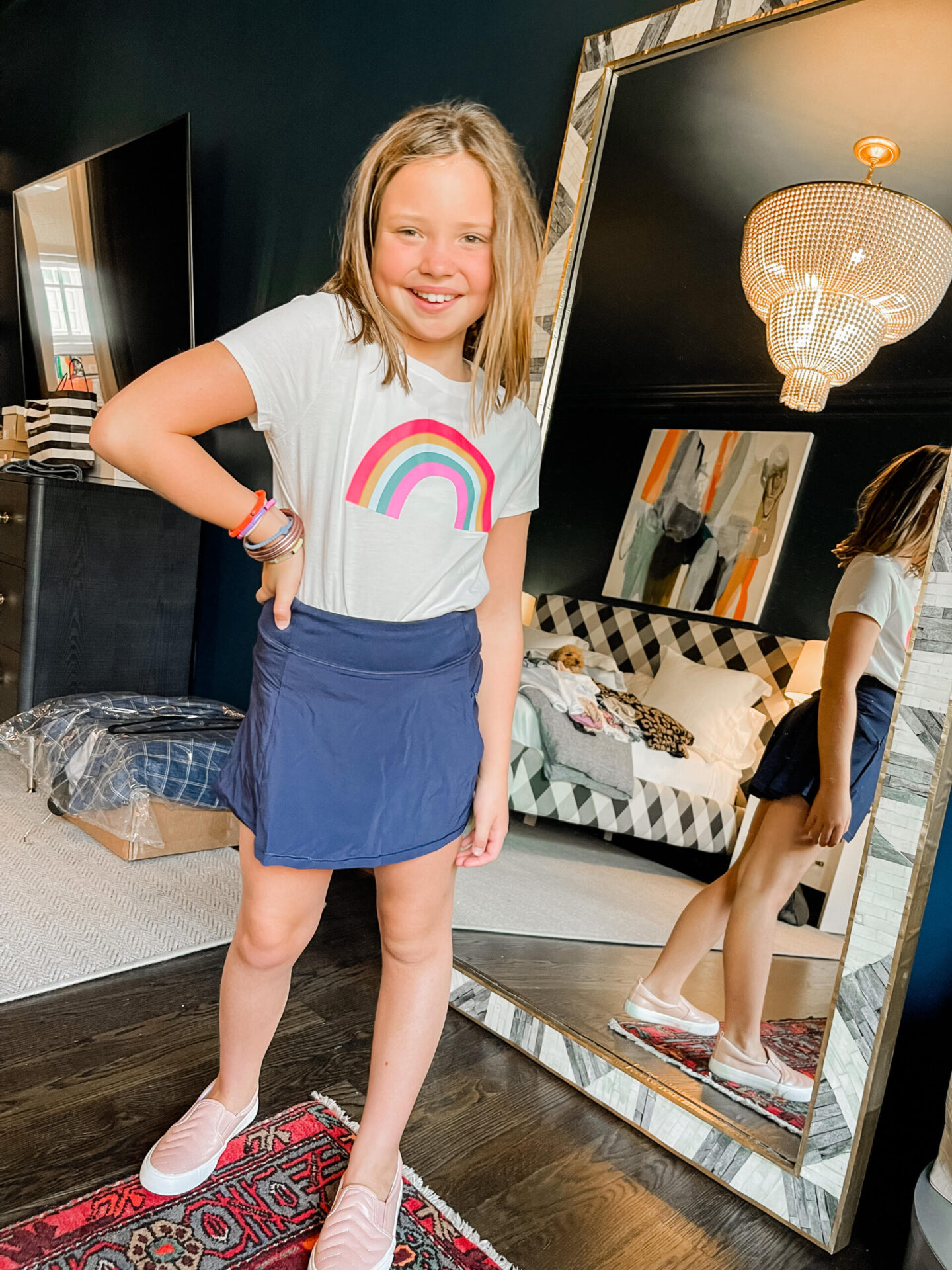 Back to School Essentials by popular Nashville lifestyle blog, Hello Happiness: image of a young girl wearing a rainbow graphic shirt and all in motion skirt with pink sneakers.
